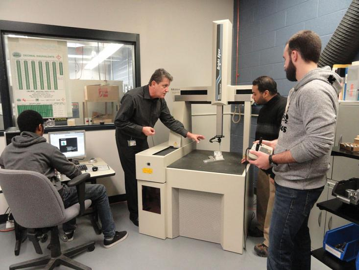 Centennial College Instructor Lucian Toma with students and CMM.